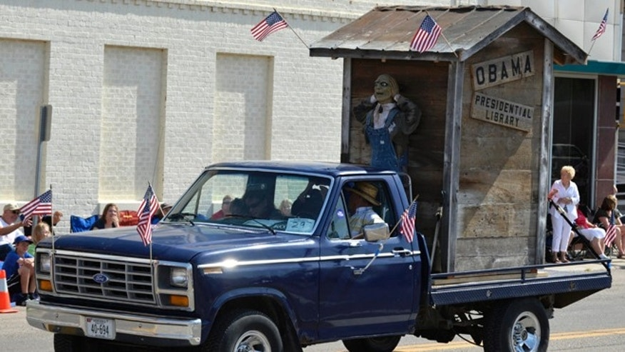 July 4, 2014: A float with the words 'Obama Presidential Library' is seen during the Fourth of July parade in downtown Norfolk, Neb. The float has received criticism from  a city councilman and the Nebraska Democratic Party, and others. (AP/NORFOLK DAILY NEWS/Darin Epperly)