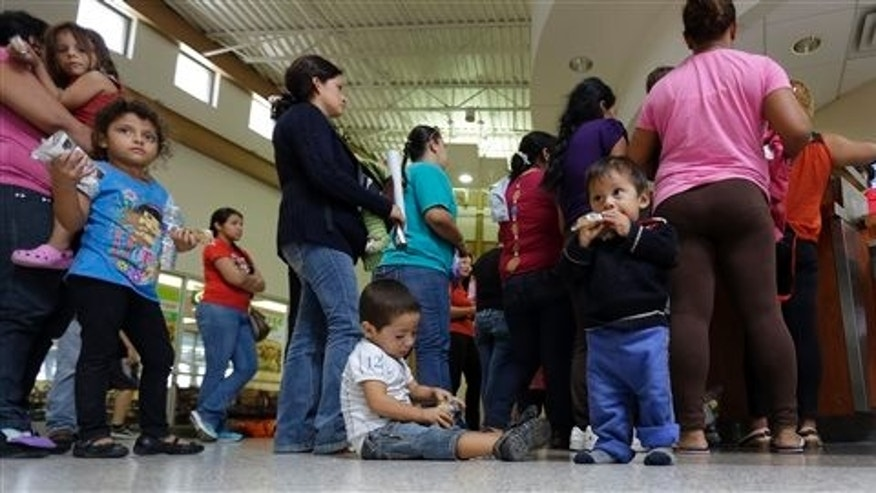 In this June 20, 2014 photo, immigrants who entered the U.S. illegally stand in line for tickets at the bus station after they were released from a U.S. Customs and Border Protection processing facility in McAllen, Texas. The immigrants entered the country through an area referred to as zone nine. (AP Photo/Eric Gay)