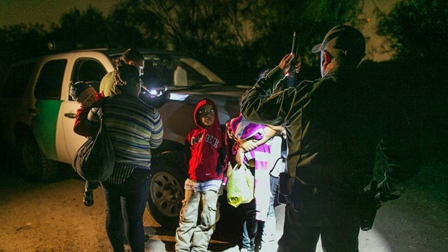 July 3, 2014: Hondurans stopped by U.S. Customs and Border Protection Services agents after crossing the Rio Grande near McAllen, Texas.