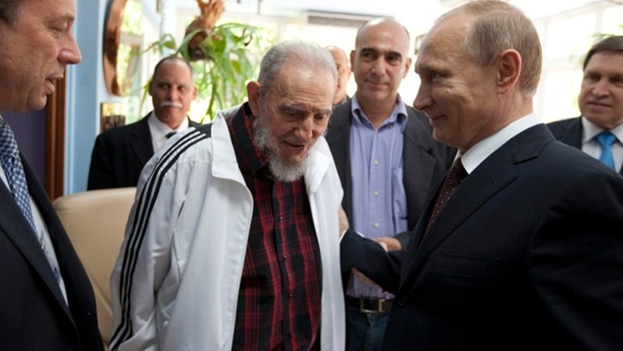 Cuba's Fidel Castro, center, meets with Russia's President Vladimir Putin, right, in Havana, Cuba, Friday, July 11, 2014. Putin began a Latin American tour aimed at boosting trade and ties in the region with a stop Friday in Cuba, a key Soviet ally during the Cold War that has backed Moscow in its dispute with the West over Ukraine. (AP Photo/Alex Castro)