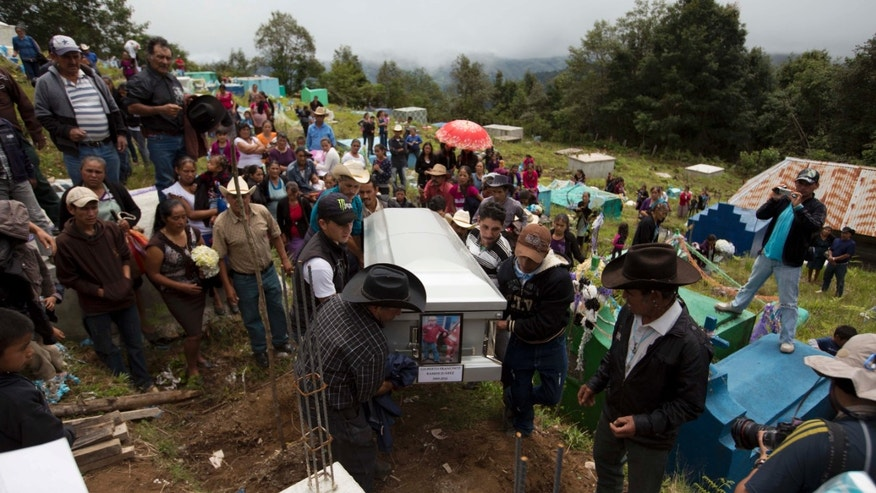 Relatives arrive at the local cemetery, carrying the coffin containing the remains of Gilberto Francisco Ramos Juarez, a Guatemalan boy whose decomposed body was found in the Rio Grande Valley of South Texas, in San Jose Las Flores, Guatemala, Saturday, July 12, 2014. The 15-year-old Guatemalan migrant was buried in his hometown Saturday, nearly a month after he became a symbol of the perils facing unaccompanied children who have been flooding illegally into the U.S. (AP Photo/Moises Castillo)