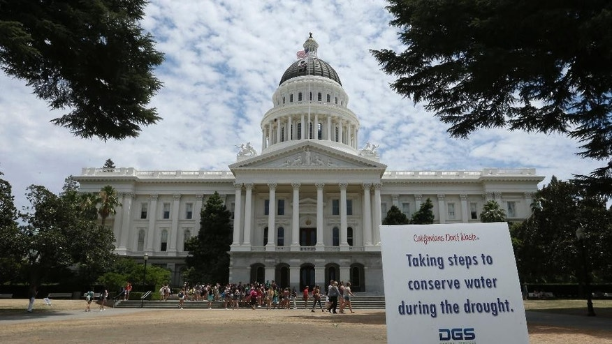 A sign alerts visitors to water conservation efforts at the state Capitol, Tuesday, July 8, 2014, in Sacramento, Calif.  State water regulators are considering fines up to $500 for excessive water use for things like irrigating lawns and car washing due to the state's severe drought. (AP Photo/Rich Pedroncelli)