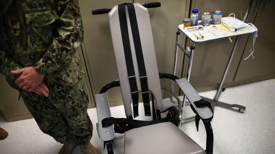 Nov. 20, 2013: A U.S. Navy nurse stands next to a chair with restraints, used for force-feeding, and a tray displaying nutritional shakes, a tube for feeding through the nose, and lubricants, including a jar of olive oil, during a tour of the detainee hospital at Guantanamo Bay Naval Base in Cuba.