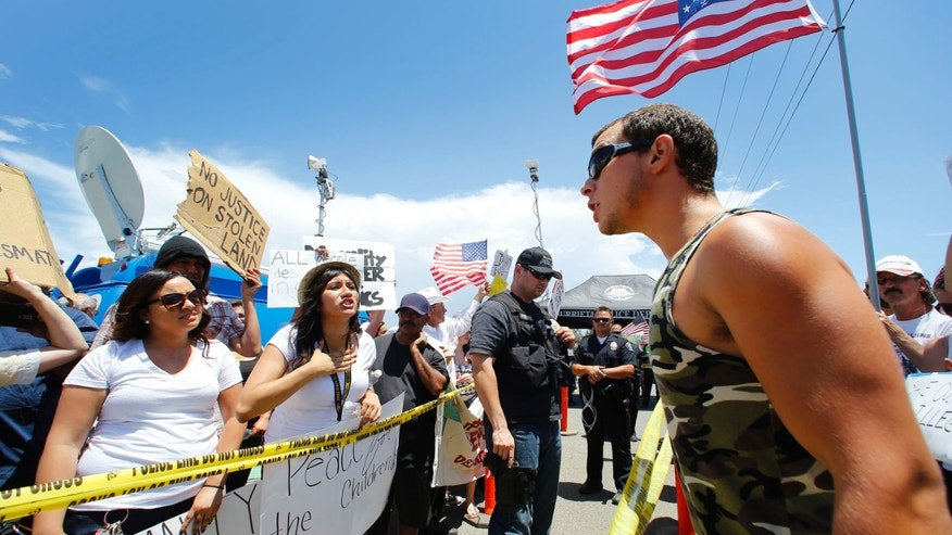 People form both sides of the issue argue across police lines during a immigration demonstration outside the Border Patrol  facility  Friday, July 4, 2014 in Murrieta, Calif. (AP Photo/The Arizona Republic, David Kadlubowski)