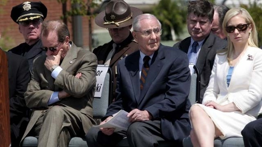 FILE - In this May 11, 2006, file photo, attending dignitaries including Oregon Gov. Ted Kulongoski, left, former Gov. Vic Atiyeh, center, and 2002 Miss America Katie Harmon sit, as the names of officers killed in the line of duty are read during the Oregon Law Enforcement Memorial ceremony at the new public-safety academy grounds in Salem, Ore. (AP Photo/Statesman-Journal, Thomas Patterson, File)