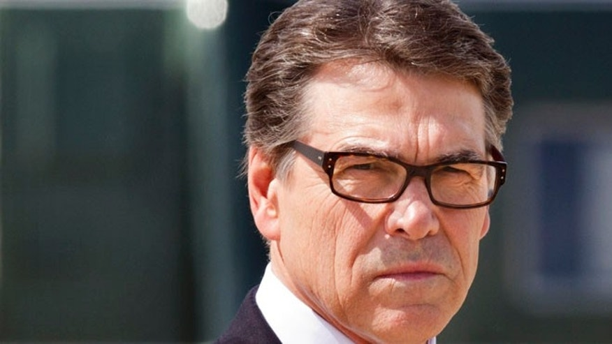 This July 9, 2014, file photo shows Texas Gov. Rick Perry as he waits to meet President Barack Obama to arrive at Dallas-Fort Worth International Airport, in Dallas.