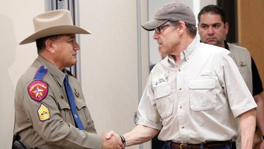 Gov. Perry with Texas Department of Public Safety spokesperson Sgt. Johnny Hernandez, June 23, 2014, in Weslaco, Texas.