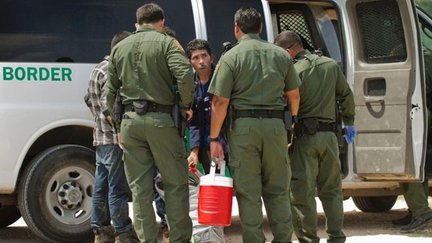 In this Thursday, July 24, 2014 photo, U.S. Border Patrol agents apprehend men who crossed the Rio Grande River from Reynosa, Tamaulipas, Mexico in Anzalduas Park in McAllen, Texas.