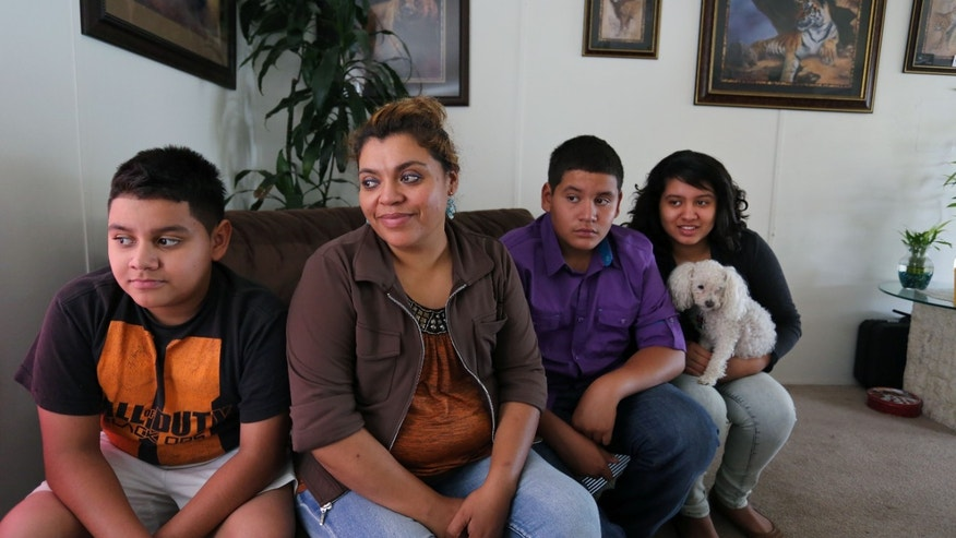 Adriana Gaytan, who came to Colorado in 1997 from the Mexican state of Zacatecas, second from left, sits at home with her children who were born in the U.S. from left to right, Osbaldo, 11, Oscar 13, Indhira, 14, and their dog Kissy, in Aurora, Colo., Thursday July 31, 2014. Gaytan will get a drivers license soon, as Colorado will begin issuing driver's licenses and identification cards to people who are in the country illegally or have temporary legal status. (AP Photo/Brennan Linsley)