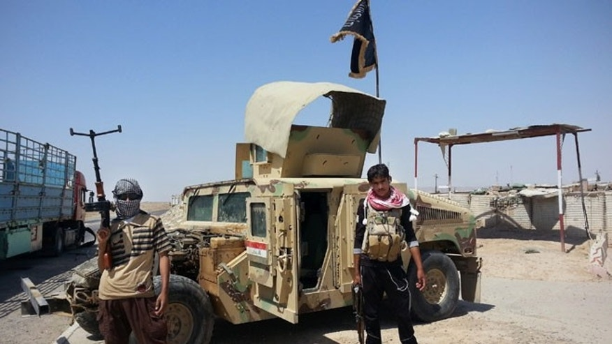 In this file photo taken Thursday, June 19, 2014, ISIS militants stand with captured Iraqi Army Humvee.