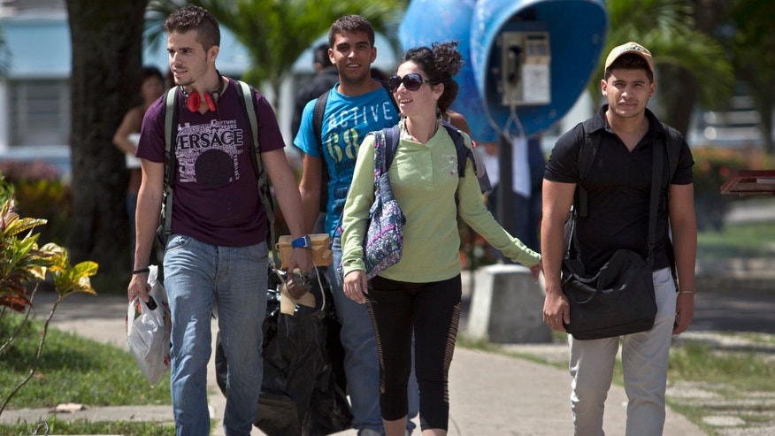 In this July 11, 2014, photo, Cuban students exit Marta Abreu Central University in Santa Clara, Cuba. Beginning as early as October 2009, a project overseen by the U.S. Agency for International Development sent Venezuelan, Costa Rican and Peruvian nationals to Cuba to cultivate a new generation of political activists. Often posing as tourists, the young travelers befriended Cuban students. Fernando Murillo, contracted to turn politically apathetic young Cubans into âchange agents,â headed to Santa Clara and connected with a cultural group that called itself âRevolution,â a modest outfit of street artists devoted to electronic music and video. (AP Photo/Franklin Reyes)