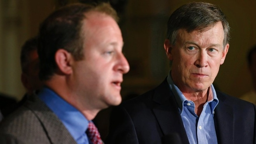 Colo. Gov. John Hickenlooper, right, listens as U.S. Rep. Jared Polis, D-Colo., takes questions during a news conference about fracking, at the Capitol, in Denver, Monday, Aug. 4, 2014. During the news conference Hickenlooper announced the creation of a task force charged with crafting recommendations to help minimize land use conflicts that can occur when siting oil and gas facilities near homes, schools, businesses and recreational areas. (AP Photo/Brennan Linsley)