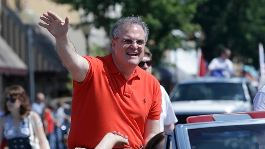 FILE - In this file photo taken June 14, 2014, incumbent Democratic U.S. Sen. Mark Pryor rides the the Pink Tomato Festival parade as he campaigns in Warren, Ark. Pryor is being challenged by Republican Congressman Tom Cotton in a campaign that began about one year ago. (AP Photo/Danny Johnston, File)