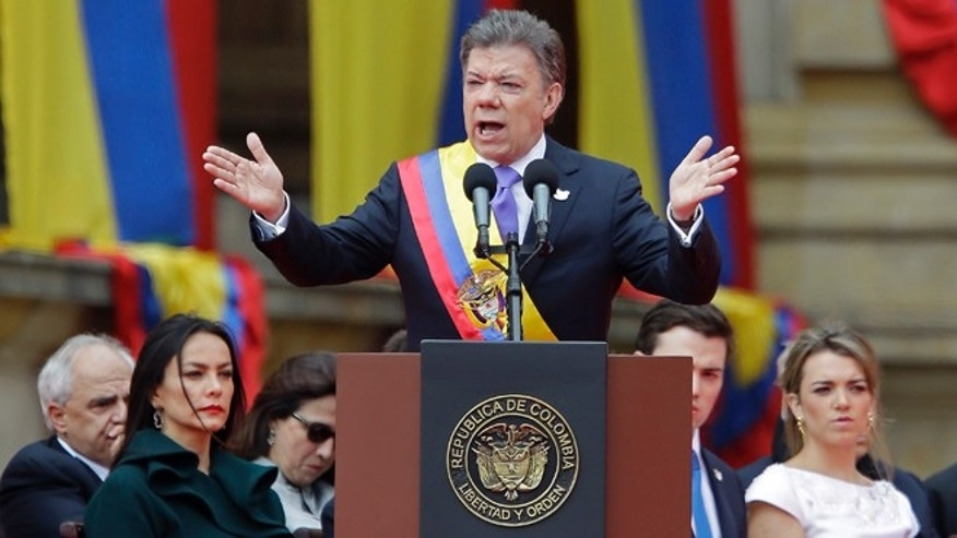 Wearing the presidential sash, newly sworn-in President Juan Manuel Santos, delivers his inaugural speech, in Bogota, Colombia, Thursday, Aug. 7, 2014. Santos, who narrowly defeated a conservative challenger to win another term, promises to redouble his efforts to end a half-century war against Marxist rebels. (AP Photo/Fernando Vergara)