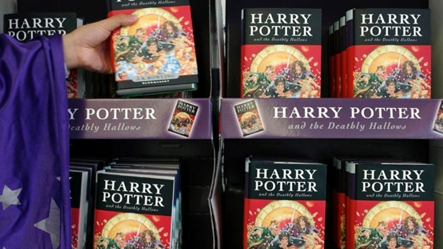 An employee dressed up as a character from the Harry Potter series grabs a copy of the seventh and final Harry Potter book.