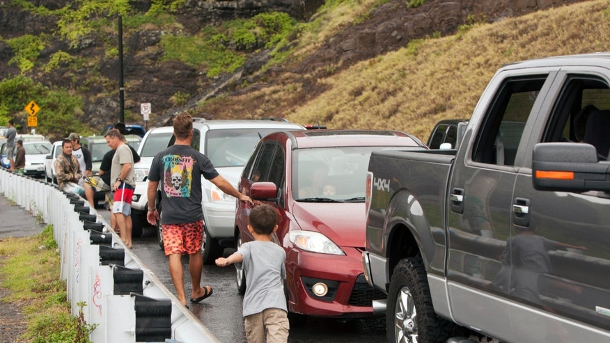 Aug. 8, 2014: Onlookers park on the side of the road to look at the waves at Makapuu Beach in Waimanalo, Hawaii.