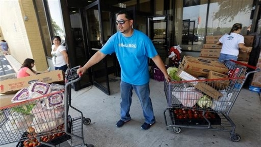 In this July 3, 2014 photo, pastor Marcus Burgos, center, helps distribute groceries at a food bank at the Abundant Life Church in San Antonio. The food bank is cosponsored by the Libre Initiative, partly funded by conservative billionaires Charles and David Koch, which is looking to make inroads with the rising voting block of Hispanics. (AP Photo/Eric Gay)