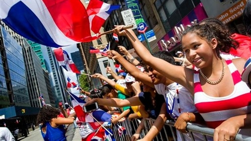 Revelers enjoy the Dominican Day Parade in New York, Sunday, Aug. 10, 2014. (AP Photo/Craig Ruttle)