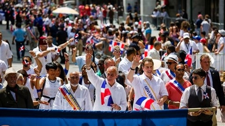 New York Governor Andrew Cuomo, lower right, marches at the front of the Dominican Day Parade in New York Sunday, Aug. 10, 2014. (AP Photo/Craig Ruttle)