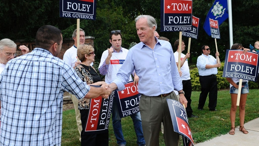 Aug. 11, 2014: Republican candidate for Connecticut governor Tom Foley, center, shakes hands with supporter Ben Ancona as he greets commuters off an exit during rush hour.