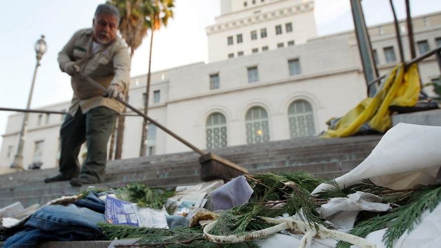 Nov. 30, 2011: City sanitation worker Gino Rodriguez sweeps plastic police handcuffs and other debris from the south steps of City Hall at the Occupy Los Angeles encampment at City Hall Park.