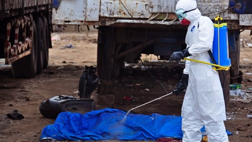 Aug. 12, 2014: The body of a man found in the street, suspected of dying from the Ebola virus, is sprayed with disinfectant in the capital city of Monrovia, Liberia.