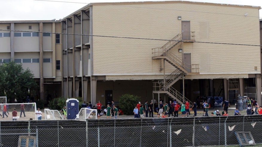 FILE - This June 23, 2014 file photo shows a temporary shelter for unaccompanied minors who have entered the country illegally at Lackland Air Force Base in San Antonio. The government said Monday it will soon close three emergency shelters it established at U.S. military bases to temporarily house children caught crossing the Mexican border alone. It said fewer children were being caught and other shelters will be adequate.  (AP Photo/Eric Gay, File)