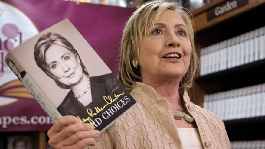 August 13, 2014: Former Secretary of State Hillary Rodham Clinton holds her memoir 'Hard Choices' at Bunch of Grapes Bookstore, in Vineyard Haven, Mass. (AP Photo/Steven Senne)