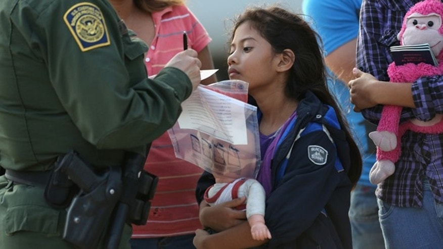 Salvadorian immigrant Stefany Marjorie, 8, watches as a U.S. Border Patrol agent records family information.
