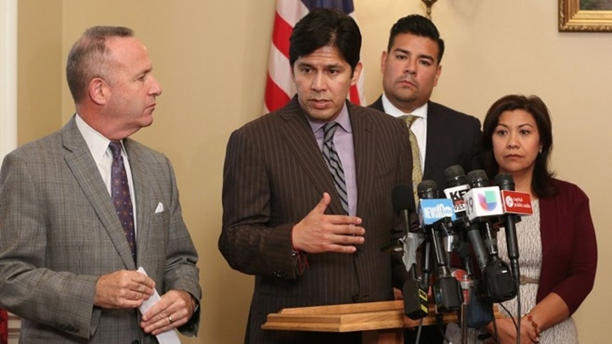 State Sen.  Kevin de Leon, D-Los Angeles, second from left, responds to a reporters question concerning a plan to provide legal help for unaccompanied children from Central American, during a Capitol news conference, Thursday, Aug. 21, 2014, in Sacramento, Calif. Supported by Gov. Jerry Brown, Attorney General Kamala Harris, legislative leaders and the Latino Legislative Caucus, the proposed legislation will provide $3 million to help the estimated 57,000 unaccompanied children who have been caught crossing into the U.S. illegally since Oct. 1.  Also seen are Senate President Pro Tem Darrell Steinberg, D-Sacramento, left, and Democratic Senators Richardo Lara, of Bell Garden, second from right, and Norma Torres, of Pomona. (AP Photo/Rich Pedroncelli)