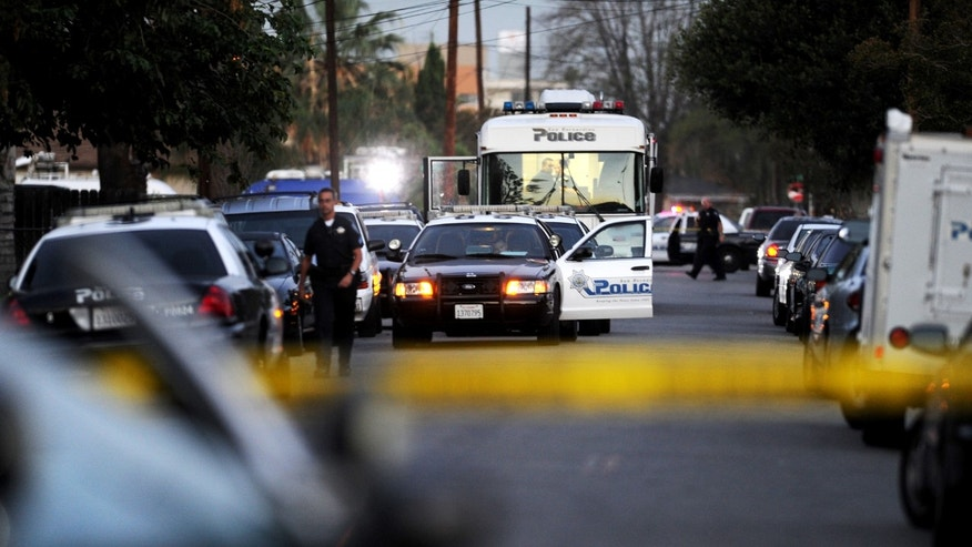 San Bernardino Detectives secure the scene where a police officer shot and killed a gunman during an early morning shootout that began after another officer was gravely wounded, Friday, Aug. 22, 2014, in San Bernardino, Calif. (AP Photo/The Sun, Micah Escamilla) MANDATORY CREDIT