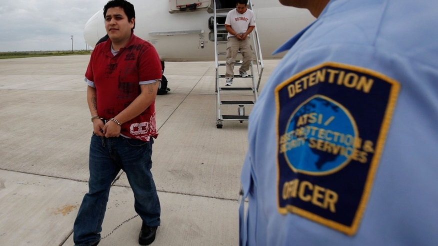 HARLINGEN, TX - MAY 25:  A security guard watches as Alberto Ortiz-Hernandez walks to a bus after getting of a deportation flight May 25, 2010 in Harlingen, Texas. Hernandez, who was deported after he was arrested for driving with a expired license, left a pregnant wife and five-year-old daughter behind. He and other undocumented Mexicans began the morning at an ICE processing center in suburban Chicago before boarding a charter flight to Harlingen, Texas where they were then bussed to Brownsville and finally walked to the Mexican border and released from custody. The U.S. deports over 350,000 immigrants a year for entering the country illegally, most are Mexican, and more than 90 percent are men.  (Photo by Scott Olson/Getty Images) *** Local Caption *** Alberto Ortiz-Hernandez