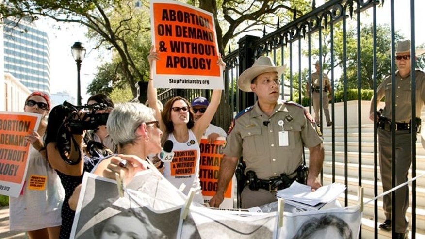 Aug 25, 2014: Pro-abortion rights activists chant slogans while a Texas Department of Public Safety trooper removes their signs from the gate of the Governor's Mansion in Austin, Texas.