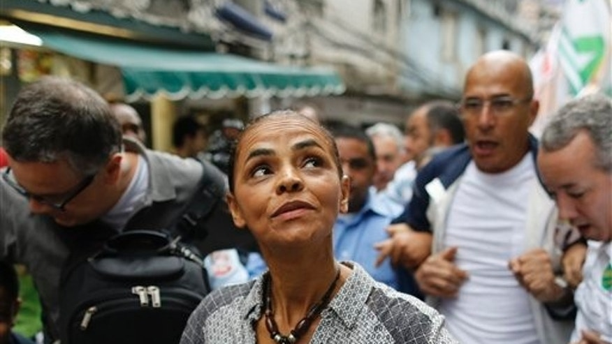 Marina Silva, presidential candidate for the Brazilian Socialist Party, campaigns in the Rocinha slum of Rio de Janeiro, Brazil, Saturday, Aug. 30, 2014. Silva is leading polls in her race against current President Dilma Rousseff and tapping into the widespread frustrations of many Brazilians with a sputtering economy and poor public services, angst that fueled last year's massive anti-government protests. Brazil will hold its presidential election on Oct. 5. (AP Photo/Leo Correa)