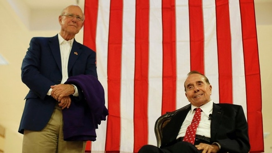In this Monday, Sept. 22, 2014 photo, Republican Sen. Pat Roberts listens while former Senate Majority Leader Bob Dole, right, speaks during a campaign stop at a mall in Dodge City, Kan.