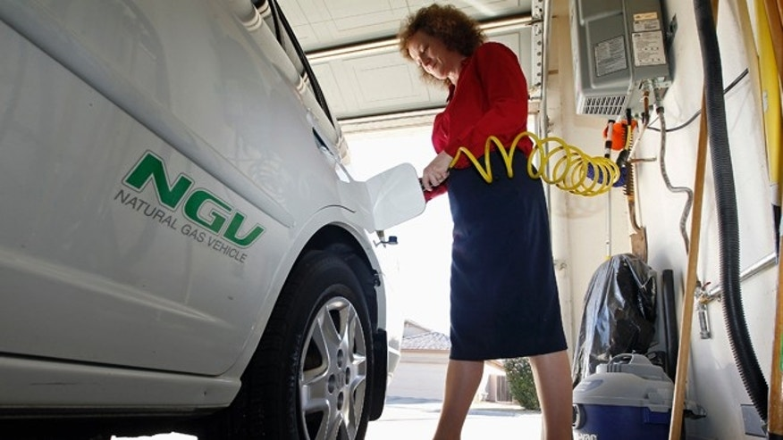 FILE: October 3, 2013. A woman connects the nozzle of a home refueling station to her 2003 natural gas powered Honda Civic, Chandler, Ariz.