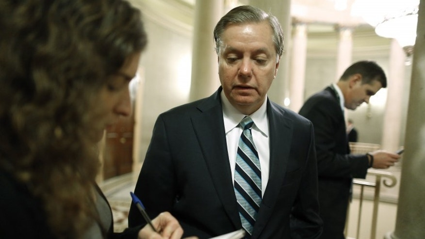 Sen. Lindsey Graham talks to a reporter as he arrives for a Republican Senate caucus meeting at the U.S. Capitol in Washington, Oct. 16, 2013. (REUTERS/Jonathan Ernst)