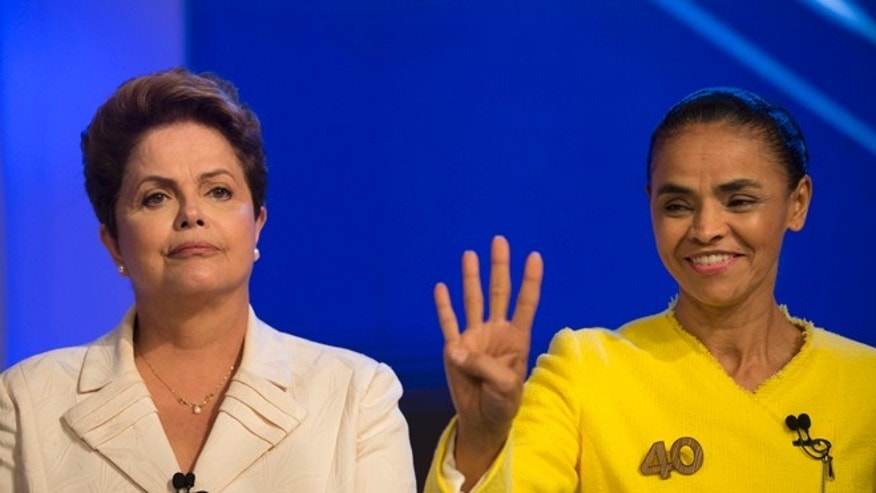 Brazil's President Dilma Rousseff, presidential candidate for re-election of the Workers Party, PT, left, poses for a photo next to Marina Silva, presidential candidate of the Brazilian Socialist Party, PSB, as they arrive for a televised presidential debate in Rio de Janeiro, Brazil, Thursday, Oct. 2, 2014. Brazil will hold general elections on Oct. 5. (AP Photo/Felipe Dana)