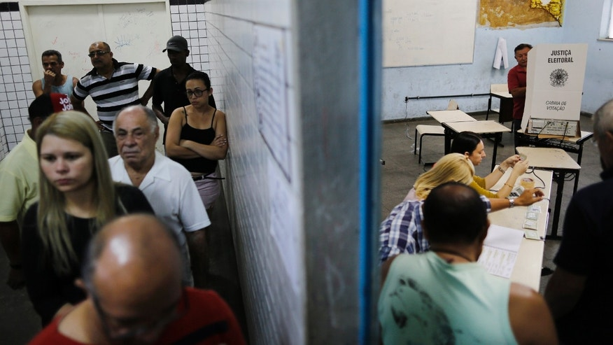 People wait in line, left, as a man votes during general elections at a school in the Nova Holanda slum inside the complexo da Mare in Rio de Janeiro, Brazil, Sunday, Oct. 5, 2014. Brazilians are casting ballots in a presidential election expected to force a three-week runoff campaign between incumbent Dilma Rousseff and one of her two top challengers, either former environment minister and senator Marina Silva or Aecio Neves. Brazilians are also deciding congressional races and electing governors. (AP Photo/Leo Correa)