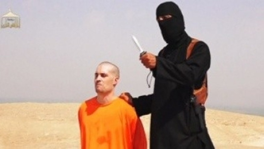 A masked Islamic State militant holding a knife speaks next to U.S. journalist James Foley at an unknown location in a still from a video posted online by the terror group.