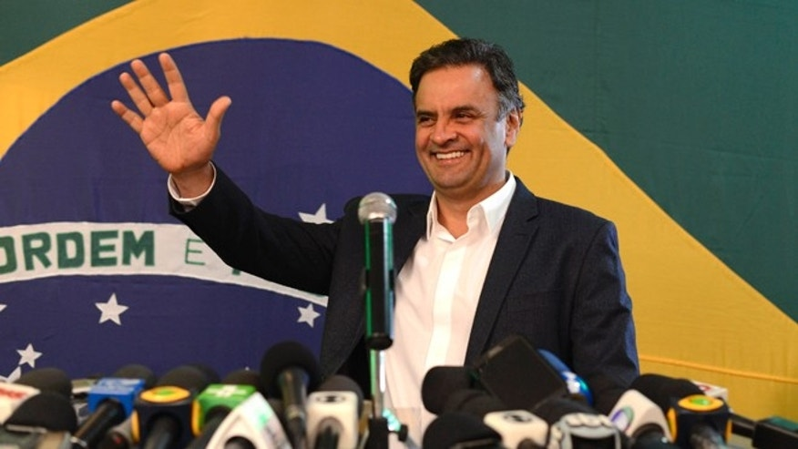 Aécio Neves, presidential candidate of the Brazilian Social Democracy Party, PSDB, waves during a press conference in Belo Horizonte, Brazil, Sunday, Oct. 5, 2014. Official results showed Sunday that President Dilma Rousseff will face challenger Aécio Neves in a second-round vote in Brazil's most unpredictable presidential election since the nation's return to democracy nearly three decades ago.(AP Photo/Eugenio Savio)