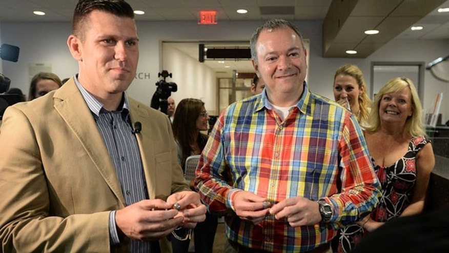 Oct. 10, 2014: Wake County Sheriffs Deputies Chad Biggs, 35, left, and Chris Creech, 46, hold their wedding rings as they say their vows before Wake County Magistrate Dexter Williams at the Wake County Courthouse in Raleigh, N.C. (AP)