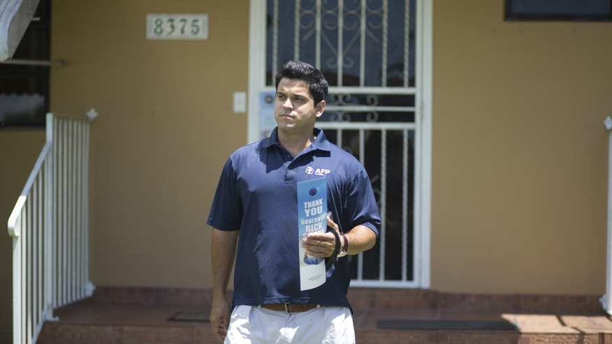 In this Aug. 12, 2014 photo, Andres Malave walks the street of a west Miami neighborhood. He started the day huddled with about a dozen volunteers in a Cuban restaurant here, offering them a last-minute pep talk before they went out to meet with voters. Itâs a strategy playing out in New England diners, Midwest truck stops and West Coast cafes: coordinators for Americans for Prosperity conservative organizers train and send out volunteers armed with an iPad and an interest in helping fellow activists shift Americaâs politics in their direction. These volunteers ground troops make up the backbone of Americans for Prosperity, the flagship organization of the political network overseen by industrialist billionaires Charles G. and David H. Koch. (AP Photo/J Pat Carter)