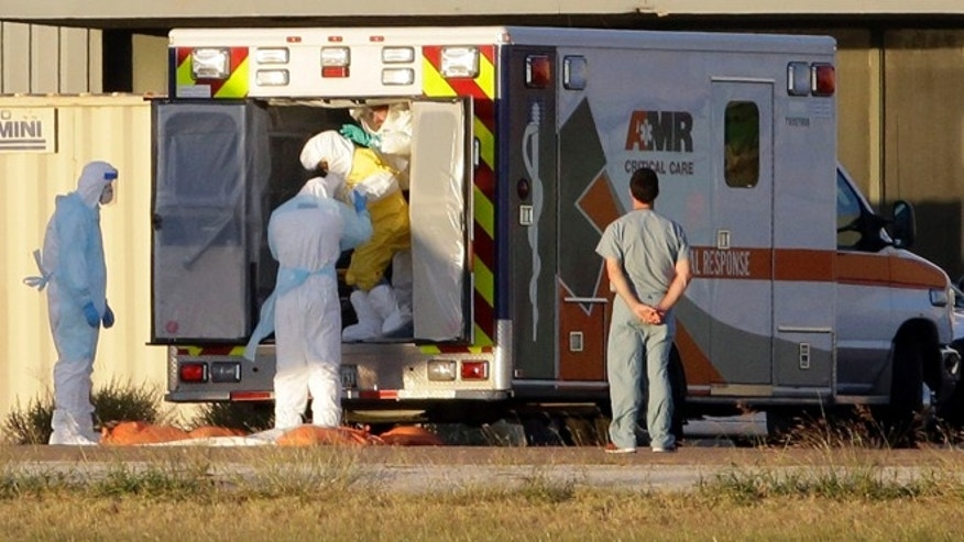 Medical staff in protective gear escort Nina Pham, exiting the ambulance, to a nearby aircraft at Love Field, Thursday, Oct. 16, 2014, in Dallas, Texas.