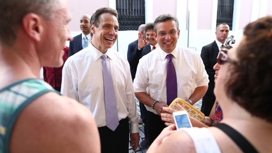 New York Gov. Andrew Cuomo, left, and Puerto Rico Gov. Alejandro Garcia Padilla talk to people during Cuomo's visit in San Juan, Puerto Rico, Friday, Oct. 17, 2014. Cuomo took his campaign for a second term to the Caribbean Friday with stops in the Dominican Republic and Puerto Rico, two places with significant ties to the state Cuomo governs. (AP Photo/Jose R. Madera)