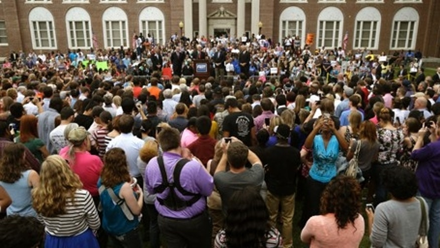 In this Oct. 6, 2014 file photo, students and others gather in front of Old Main at the University of Central Arkansas in Conway, Ark., to hear former President Bill Clinton, center, and Democratic political candidates speak.