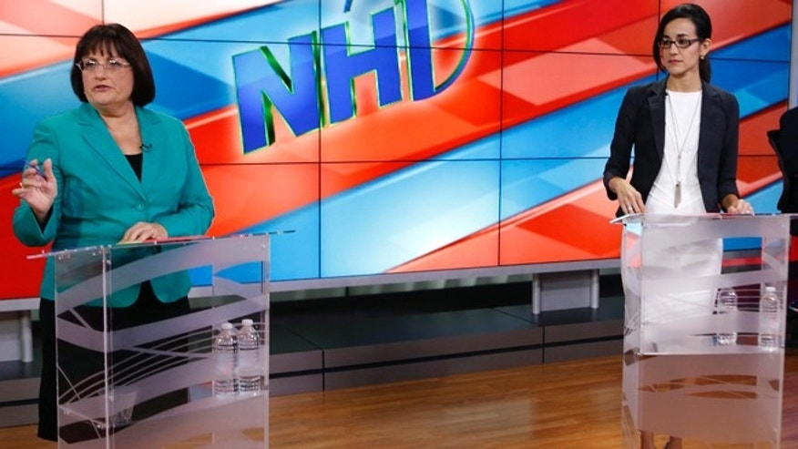 Rep. Annie Kuster, D-N.H.,  left, and Republican Marilinda Garcia prepare for a live televised debate and hosted by NH1 News on WBIN TV, Monday, Oct. 20, 2014 in Concord, N.H. (AP Photo/Jim Cole)