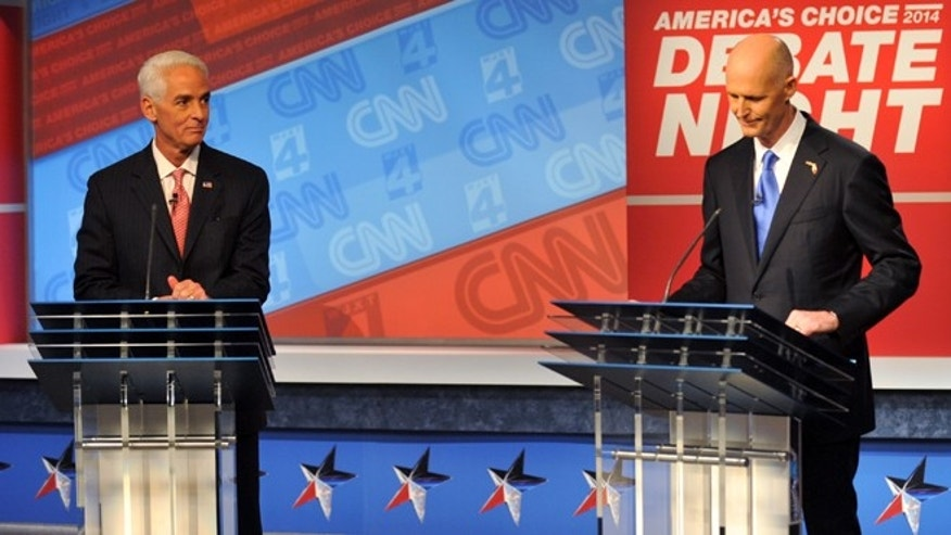 Democratic candidate Charlie Crist, left, and Republican Gov. Rick Scott wait for their live televised debate, Tuesday, Oct. 21, 2014 hosted by WJXT-TV and CNN at the Channel 4 studios in Jacksonville, Fla. (AP Photo/The Florida Times-Union, Will Dickey, Pool)