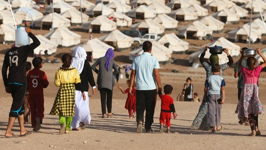 Aug. 22, 2014: Displaced people from the minority Yazidi sect, who fled violence in the Iraqi town of Sinjar, walk in Bajed Kadal refugee camp south west of Dohuk province