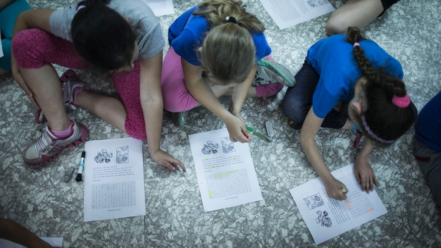 "NAZARETH-ILIT, ISRAEL - MAY 27 : Israeli schoolchildren do classwork while in a bomb shelter at their school during the Home Front drill ""Turning Point 7"" on May 27, 2013 in Nazareth-Ilit, Israel. The nationwide exercise tests the civilian population's response to a possible massive rocket attack from three fronts. (Photo by Ilia Yefimovich/Getty Images)"